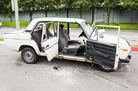hijacked: Saint-Petersburg, Russia - August 6, 2016: Crushed white VAZ-2106 car with broken windows and smashed doors, side view