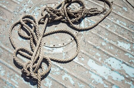 cable tangle: Knotted mooring rope lying on grungy boat deck Stock Photo