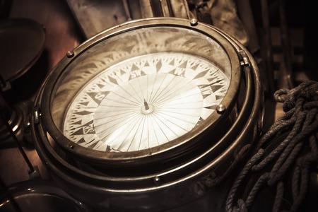 Vintage nautical compass, closeup photo with selective focus and warm retro tonal correction photo filter effect