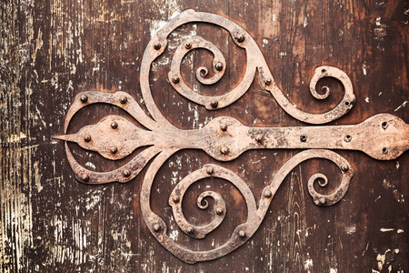 Old rusted forged decorative door hinge on vintage wooden board, closeup photo texture with retro tonal correction photo filter effect Stock Photo