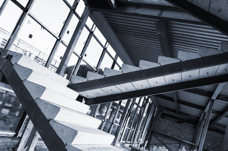 edificio industrial: Generic industrial building is under construction. Interior fragment with unfinished concrete stairway, blue toned photo with selective focus