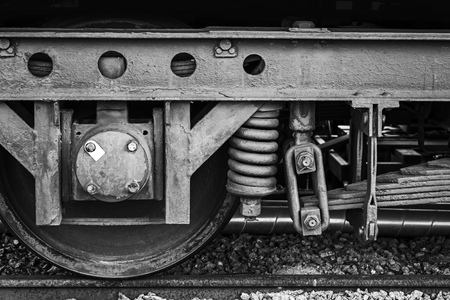 elliptic: Old rusted railway carriage wheel with suspension details, stylized black and white photo