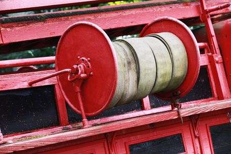 antique fire truck: Old red fire hose reel, closeup photo with selective focus Stock Photo