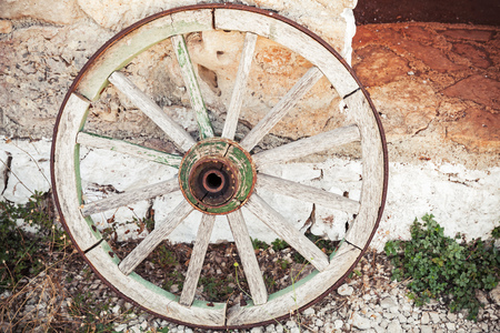 spokes: Old wooden wheel stands near stone rural wall