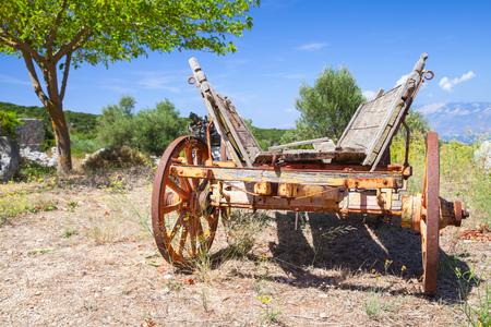 carreta madera: Vacío viejo vagón de madera rural se encuentra en el campo de verano bajo el cielo nublado. la isla de Zakynthos, Grecia