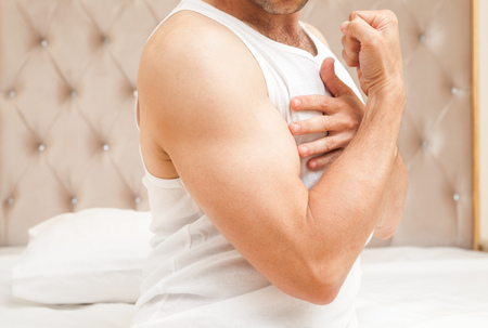Young sporty Caucasian man torso in white shirt shows his biceps in bedroom Stock Photo