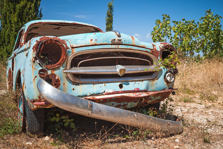 Zakynthos, Greece - August 20, 2016: Old abandoned rusted car stands in summer garden, closeup photo
