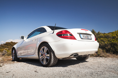 Zakynthos, Greece - August 20, 2016: White Mercedes-Benz SLK 200 pre-facelift car stands on the roadside in summer, closeup rear view Editorial