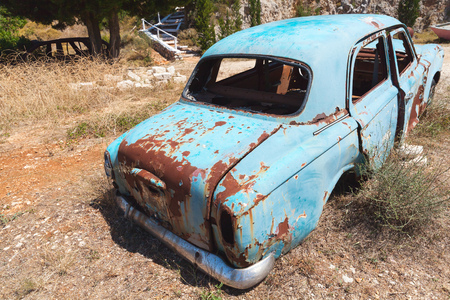Old abandoned rusted car stands in summer garden, rear view Editorial