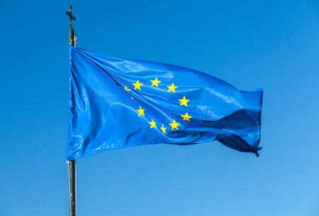 flagpole: Flag of Europe, or European Flag waving on a flagpole over clear blue sky background