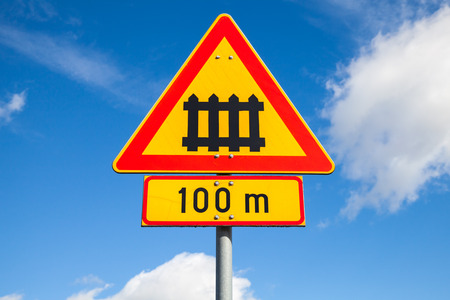 roadsign: Sweden railway crossing with gate sign. Triangular warning roadsign with red border and 100m distance label over blue cloudy sky background Stock Photo