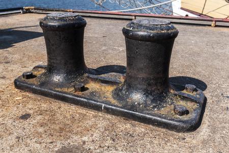 bollard: Big black mooring bollard mounted on concrete pier in port Stock Photo