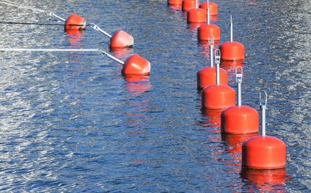 nautical equipment: Small red mooring buoys in a row, European marina, nautical equipment Stock Photo