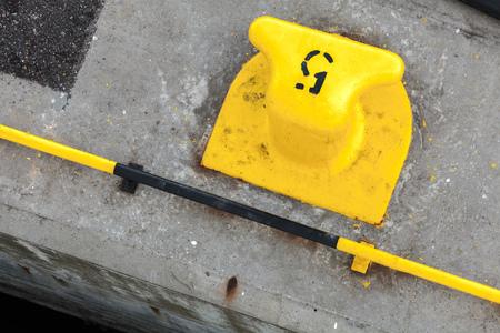 bollard: Yellow port mooring bollard with number 5 label on it