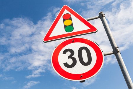 metal post: Traffic lights and speed limit 30 km per hour mounted on metal post. Road signs over blue sky background