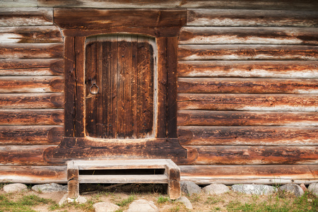Small closed door in wall made of rough logs. Traditional rural Russian architecture details