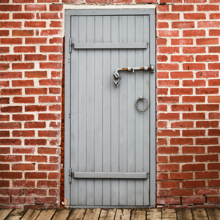 locked the door locked: Locked gray wooden door in old red brick wall, square background photo texture Stock Photo