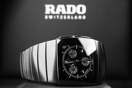 cronógrafo: San Petersburgo, Rusia - 18 de junio de 2015: Rado Sintra Chrono, reloj cronógrafo para hombre hecha de cerámica de alta tecnología con cristal de zafiro en el fondo negro con el logotipo de la empresa. enfoque selectivo