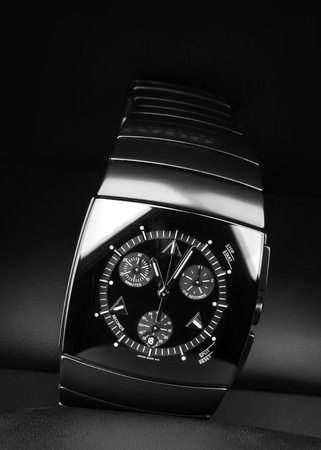 the chronograph: Mens chronograph watch made of high-tech ceramics with sapphire glass over black background. Selective focus Foto de archivo