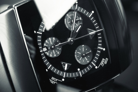 the chronograph: Mens chronograph wirstwatch made of high-tech ceramics with sapphire glass over black background. Macro photo with selective focus