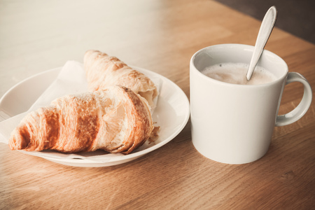 tonal: Cappuccino with croissant. White cup of coffee with milk foam stands on wooden table, closeup photo with soft selective focus. Vintage tonal correction filter, old style photo effect Stock Photo