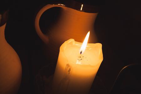 jarra de cerveza: La quema de velas y de la arcilla de la vendimia tazas de cerveza en la mesa en el restaurante de edad