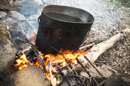 sooty: Old sooty black pan with boiling water stands on a bonfire Stock Photo