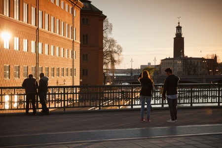 sightsee: Stockholm, Sweden - May 4, 2016: Tourists on Riksbron. The National Bridge in central Stockholm in evening