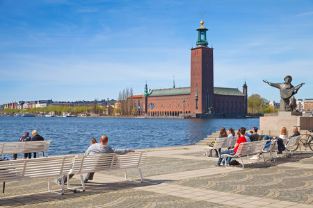 sweden resting: Stockholm, Sweden - May 5, 2016: Cityscape of central Stockholm with ordinary people relaxing near Statue of Evert Taube with Stockholm City Hall on a background