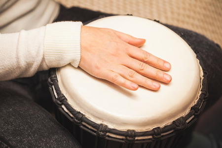 Drummer plays on African drum, closeup photo with selective focus