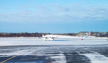 winter finland: Passenger plane goes on snowy runway field. Turku airport in winter, Finland