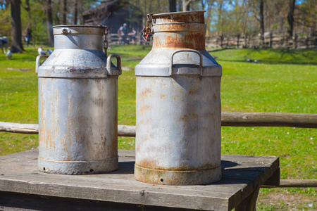 Two metal milk churns stand on wooden table over summer farm background