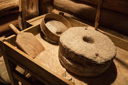 millstone: Old millstones for grinding grain, vintage farming tools