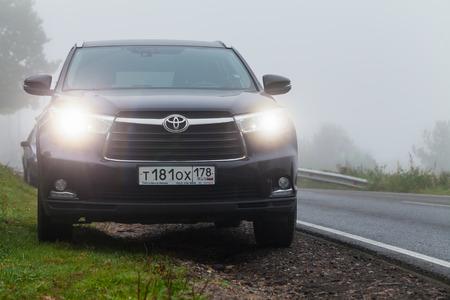 highlander: Saint-Petersburg, Russia - September 27, 2016: Black Toyota Highlander car stands on a roadside in foggy morning Editorial