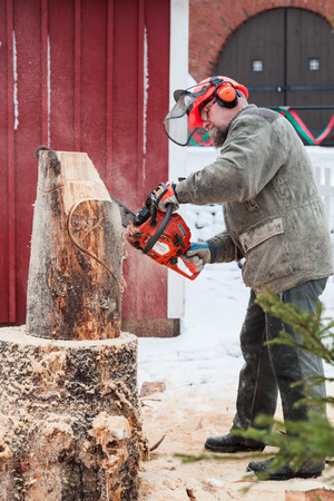 chock: Hamina, Finland - December 13, 2014: Finnish master sculptor with a chainsaw produces wooden sculpture