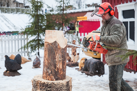winter wood: Hamina, Finland - December 13, 2014: Professional Finnish sculptor with a chainsaw produces wooden bird sculpture