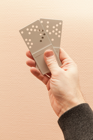 key holes: Male hand with two gray plastic door key cards with holes combination code