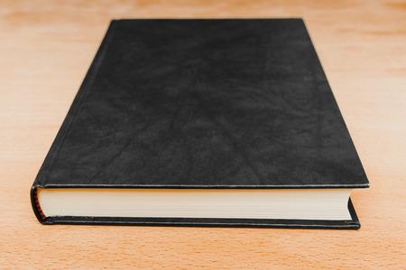 Chiuso il libro con copertina in pelle nera vuota giaceva sul tavolo di legno
