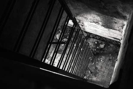Old empty abandoned bunker interior with metal ladder going down, black and white photo