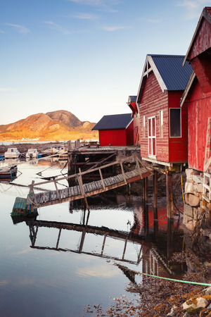 Vertical photo of Norwegian red wooden barns standing on the sea coast. Snillfjord, Sor-Trondelag region, Vingvagen fishing village