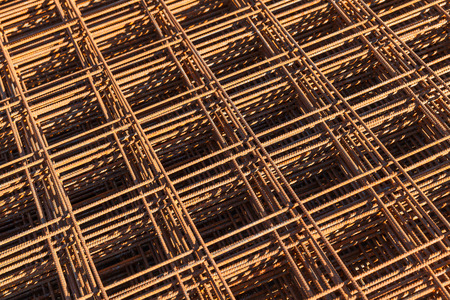 reinforcing: Abstract construction background with stacked rusted reinforcing mesh, photo with selective focus