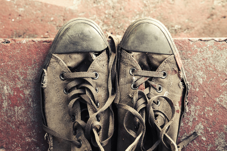 tonal: Old sneakers stand on red concrete stairs, closeup photo, top view. Retro stylized photo with tonal correction filter effect