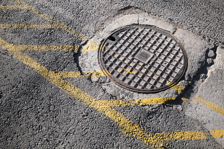Round hatch in urban pavement, sewer manhole cover with yellow road marking lines