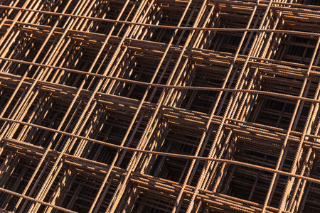 reinforcing: Abstract industrial background with stacked rusted reinforcing mesh, photo with selective focus