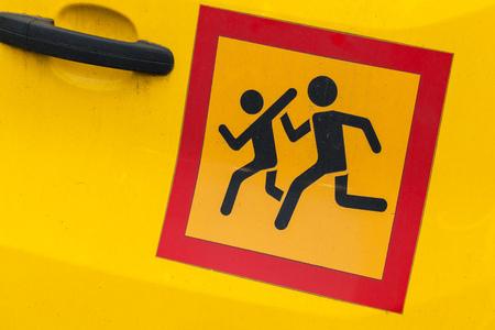 minivan: Square yellow ?aution children transportation sign in red frame, sticker on school minivan door Stock Photo