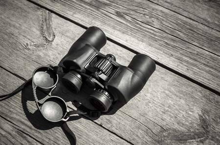 lays: Black touristic binoculars lays on rough outdoor wooden table