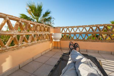 Feet of man relaxing on sun lounger, seaside balcony, popular touristic resort Zakynthos island, Greece