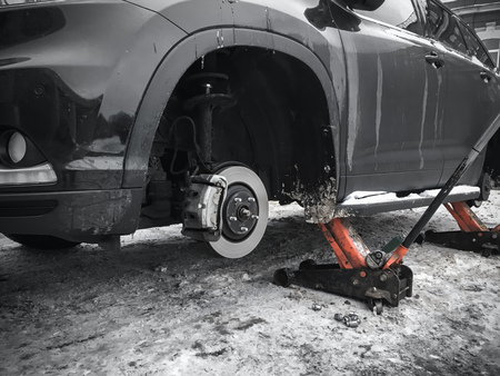 jacks: Replacing wheels on new black SUV car, two jacks hold the body in the raised position
