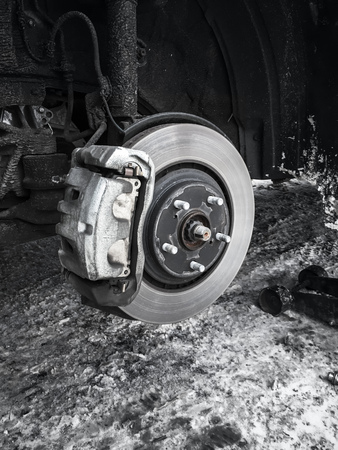 rotor: Replacing wheel on modern car, black and white photo of rotor disk with brake, selective focus Stock Photo