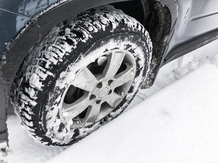 Modern car fragment, wheel with studded tire standing on winter road with deep snow, close-up photo with selective focus